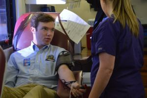 Scholar donating blood during the annual Haas Hall blood drive